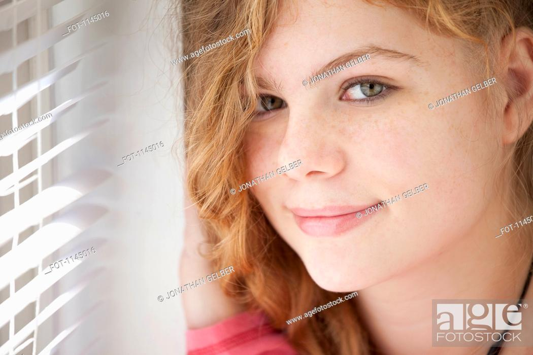 Stock Photo: Portrait of girl by window.