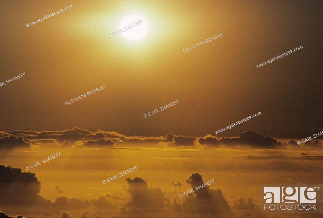 Stock Photo: Hawaii, Sunball above clouds in dramatic sunset sky.