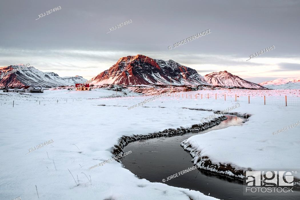 Stock Photo: Icelandic landscape in which we can see a bunch of houses and the red light of the sun setting over the mountains in the background and a river in the.