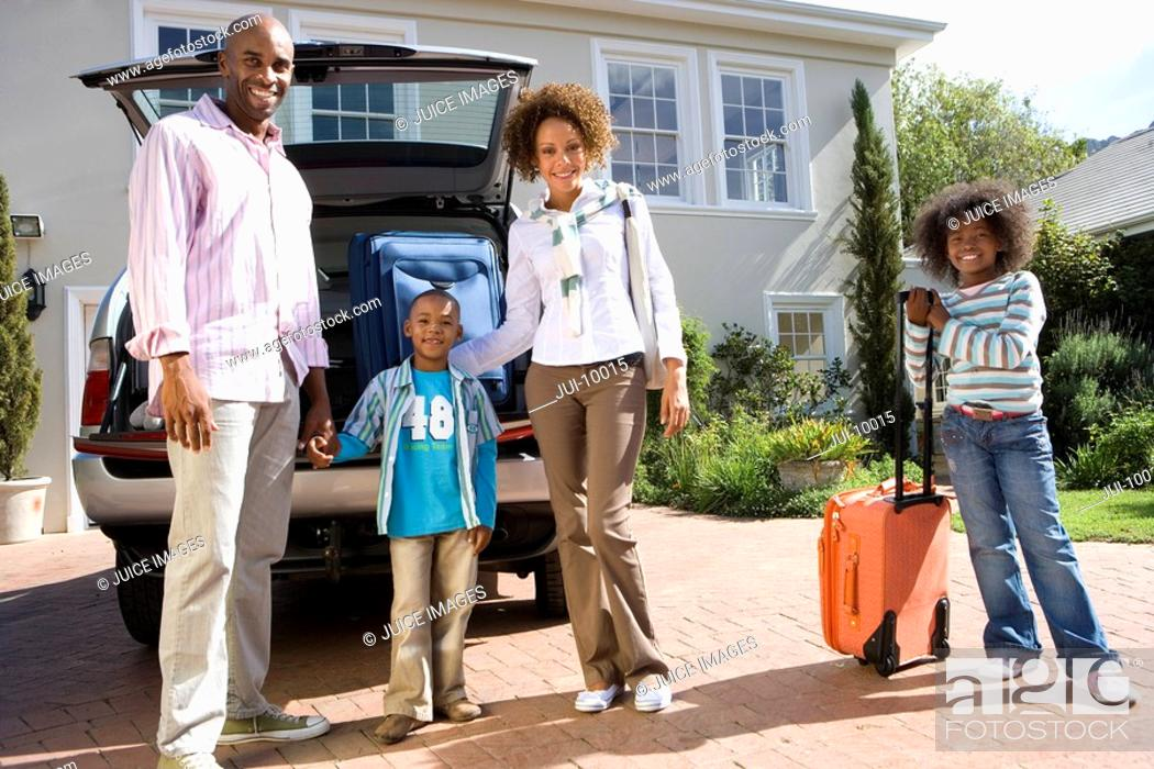 Stock Photo: Family of four with suitcases by back of car, smiling, portrait, low angle view.