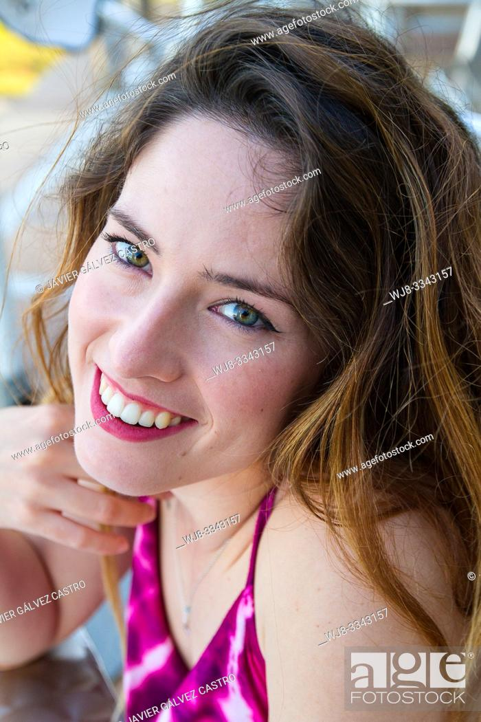 Stock Photo: young woman smiling, sitting on a terrace.