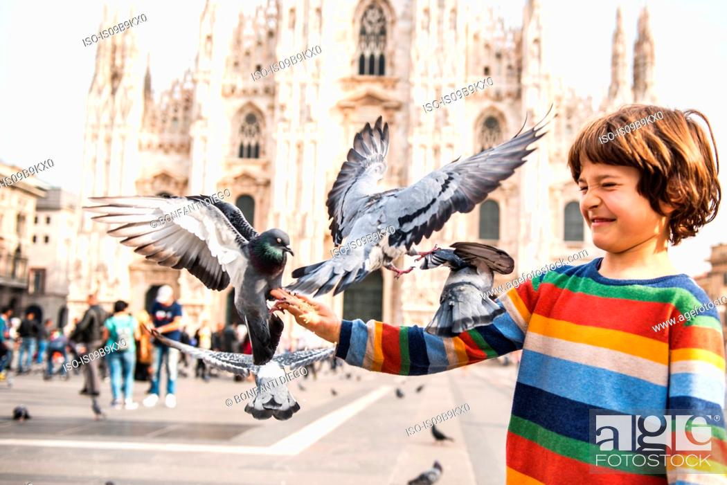 Photo de stock: Boy feeding pigeons in Milan Cathedral square, Milan, Lombardy, Italy.