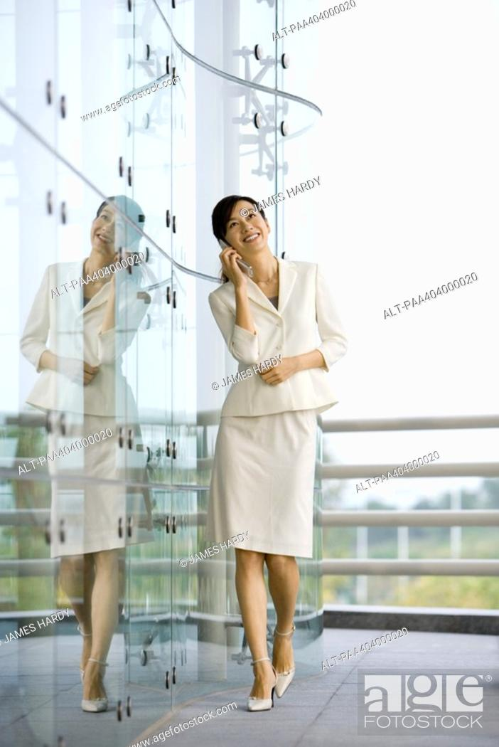 Stock Photo: Young businesswoman walking, using cell phone and smiling, full length.