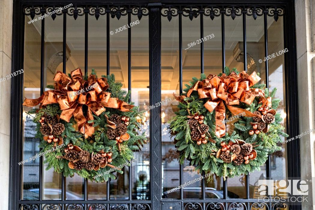 Stock Photo Christmas Wreaths With Pine Cones And Bows Gracing The Wrought Iron Covered Gl Double Entry Doors Of An Upscale Manhattan New York City
