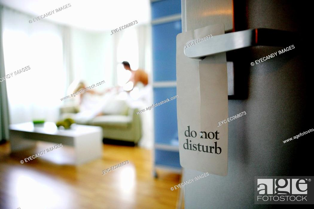 Stock Photo: Do Not Disturb sign with couple in background.