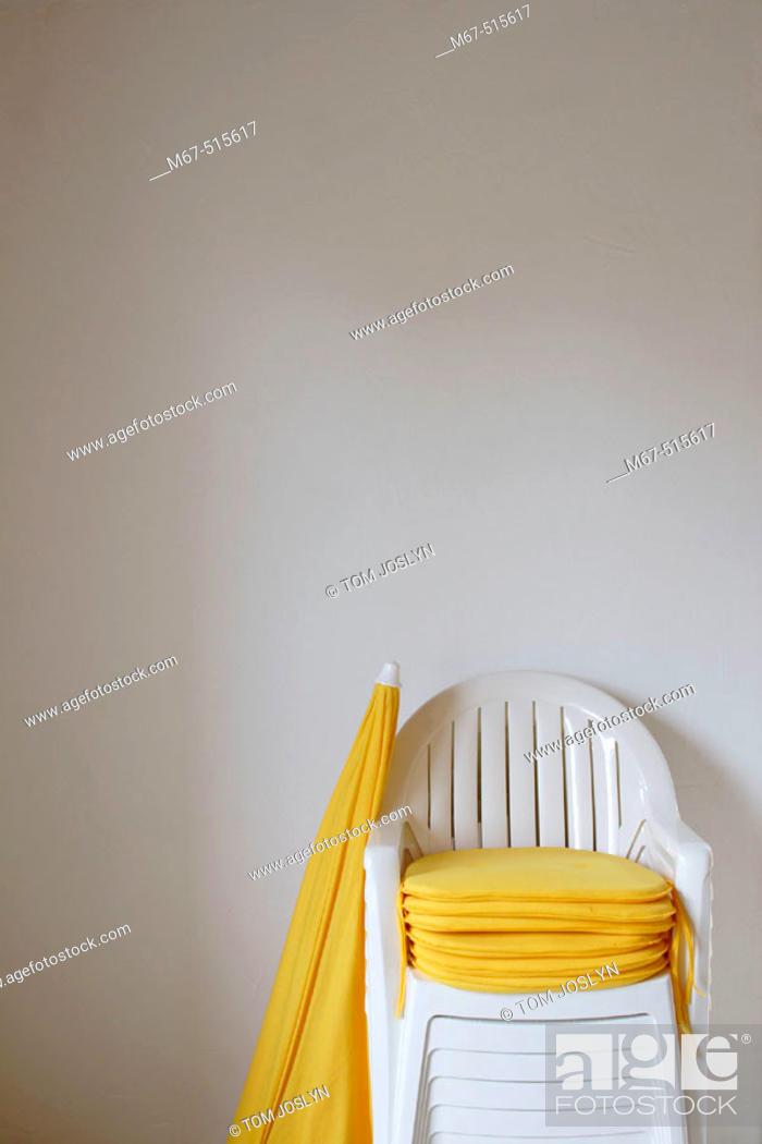 Photo de stock: Plastic garden chairs and umbrella.