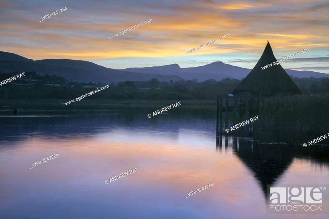 Stock Photo: The Crannog at Llangorse Lake in the Brecon Beacons National Park captured at sunset with Pen y fan in the distance. The image was captured from a nearby jetty.