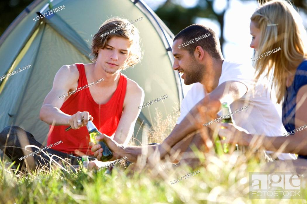 Stock Photo: Three young people sitting in front of a tent, drinking beer.