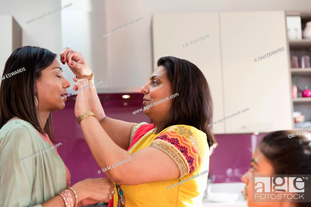 Stock Photo: Indian woman placing bind on forehead of sister.