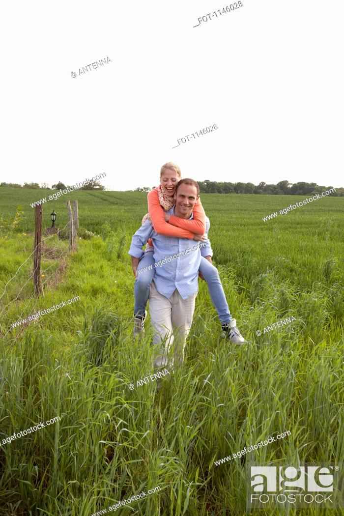 Stock Photo: A man giving his girlfriend a piggy back ride through a field.
