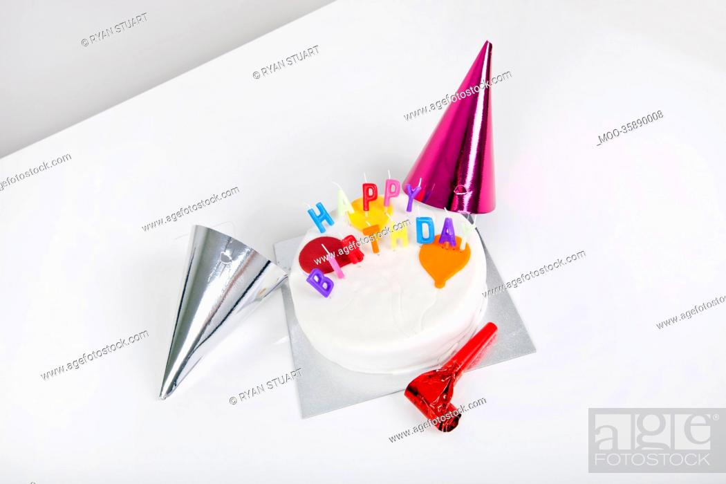 Stock Photo: Birthday cake with party hats and noisemaker on table.