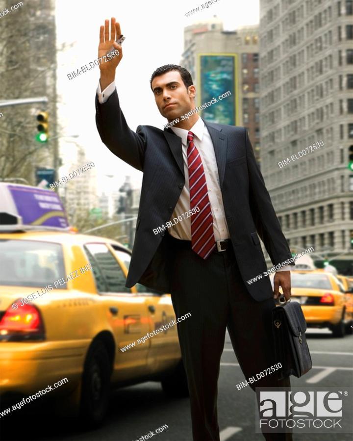 Stock Photo: Hispanic businessman hailing taxi.
