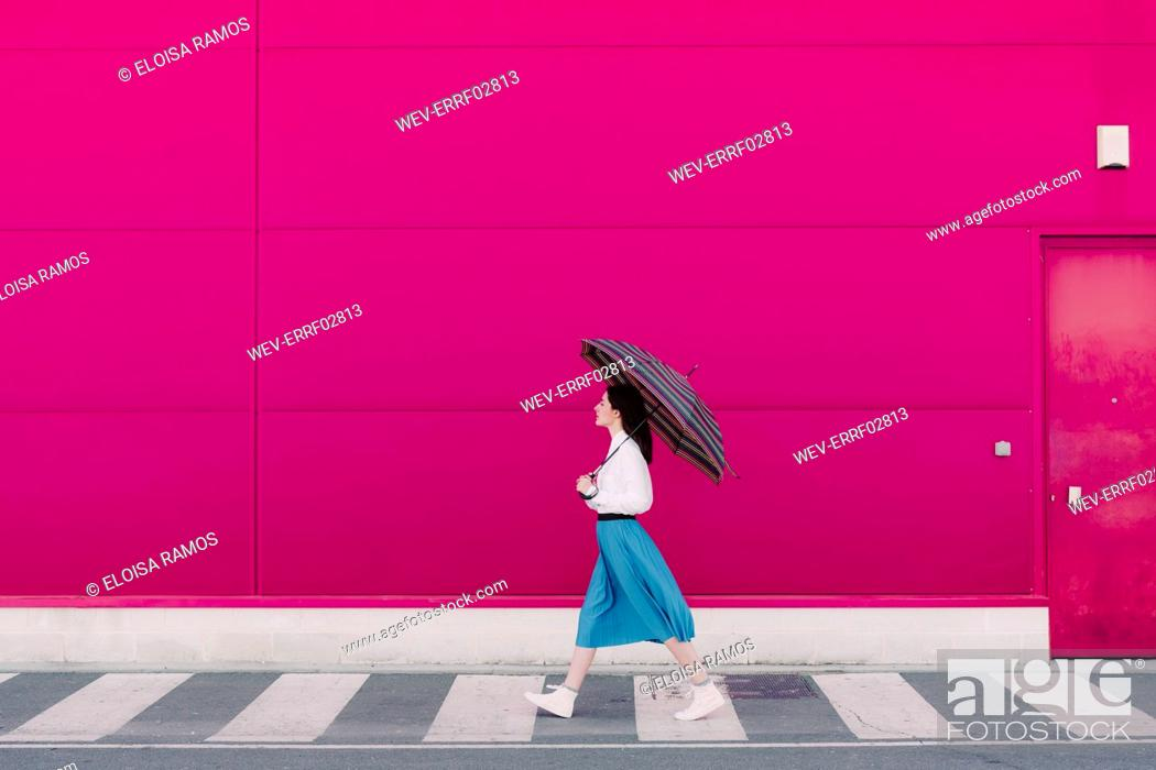 Stock Photo: Young woman with umbrella walking in front of a pink wall.