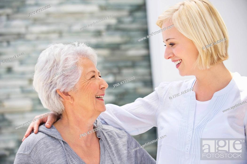 Stock Photo: Senior woman and her daughter looking at each other and smiling.