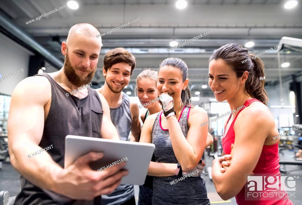 Stock Photo: Group of happy athletes with tablet after exercising in gym.