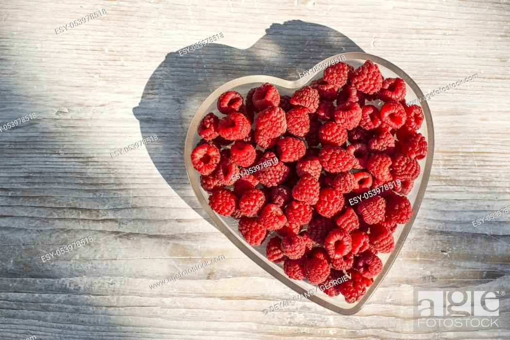 Stock Photo: Raspberries in a bowl on wood. Heart shape bowl.