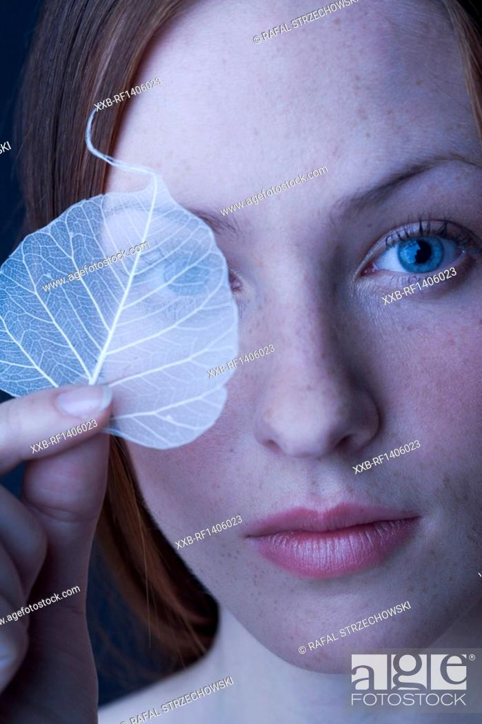 Stock Photo: woman covering eye with leaf.