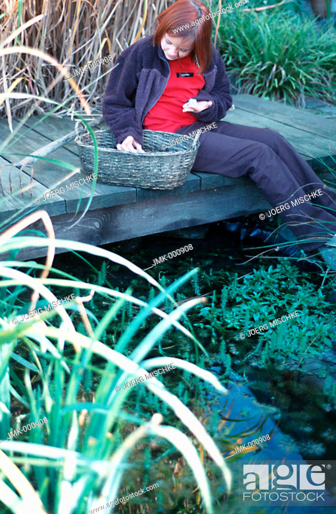 Stock Photo: Little girl in the garden, sitting on a footbridge at a pond.