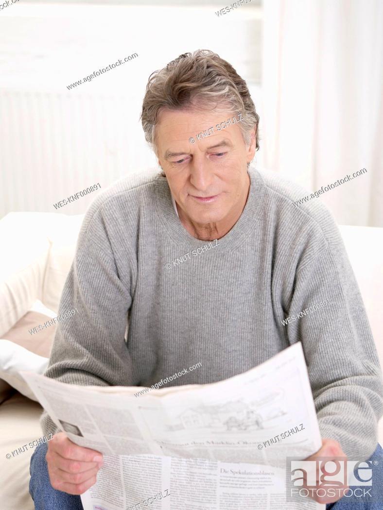 Stock Photo: Germany, Hamburg, Senior man reading newspaper.
