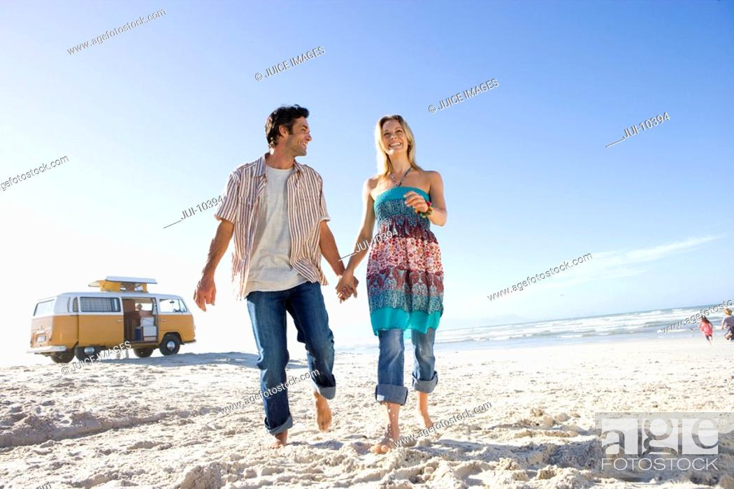 Stock Photo: Young couple on beach holding hands, camper van in background, low angle view.