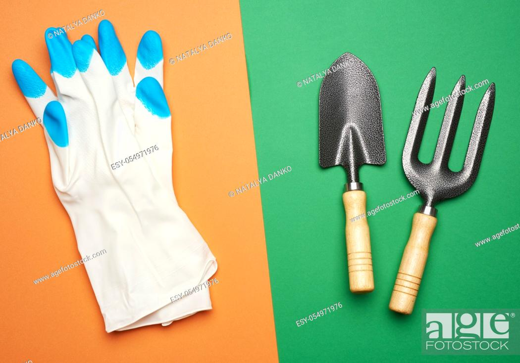 Stock Photo: white rubber gloves and garden set of shovels, rakes, pitchforks on a green-orange background, top view, flat lay.
