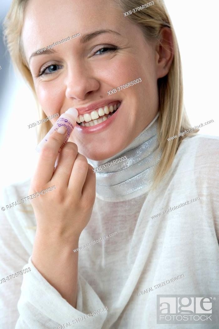 Stock Photo: woman applying lip balm.