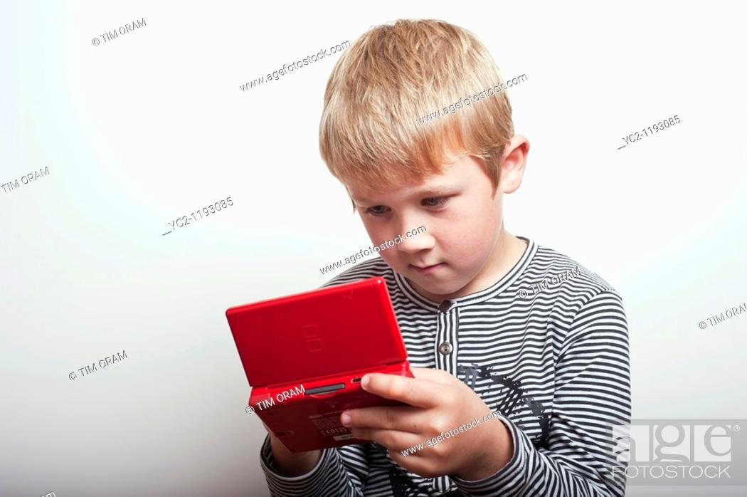 Stock Photo: 6 year old boy playing with a Nintendo DS handheld games console in the studio.