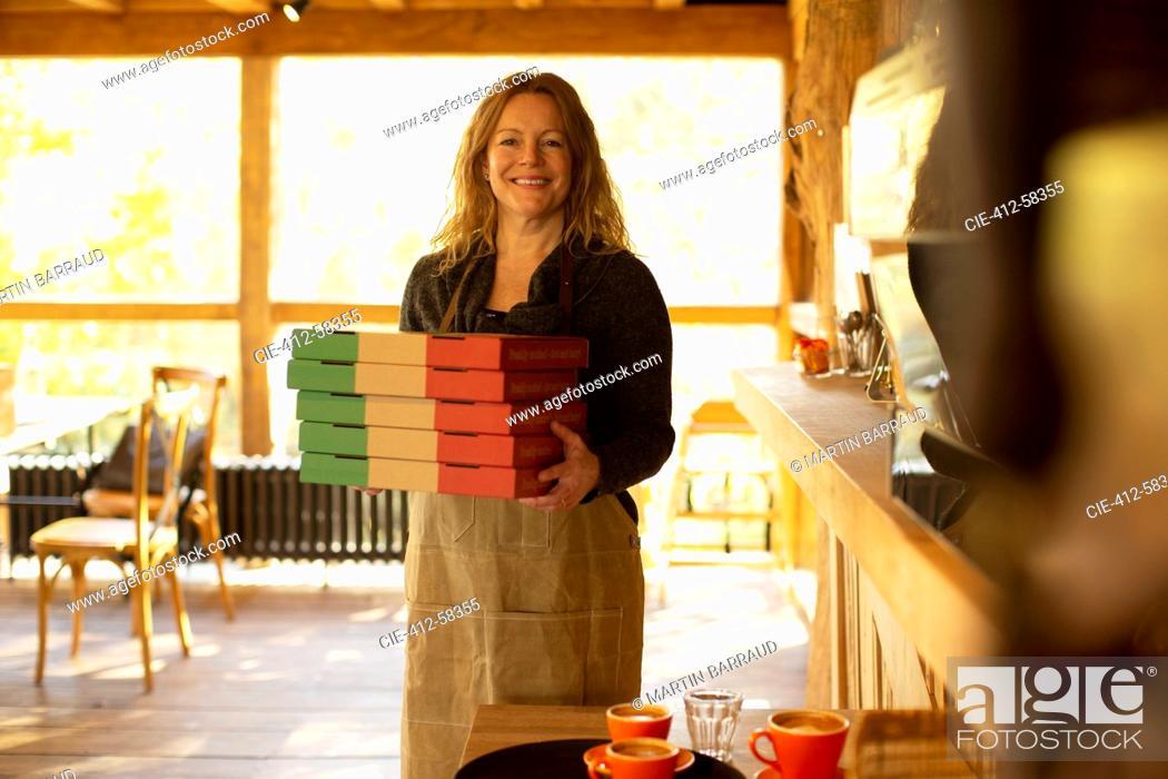 Stock Photo: Portrait happy female pizzeria owner holding pizza boxes.
