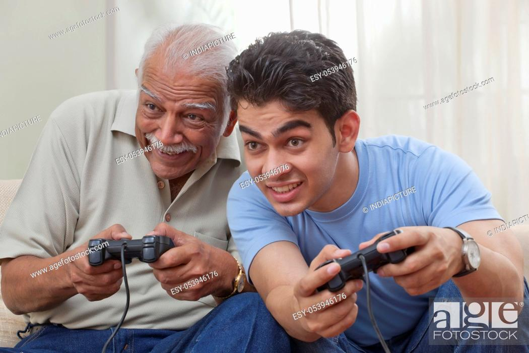 Stock Photo: Grandfather and grandson playing video game.
