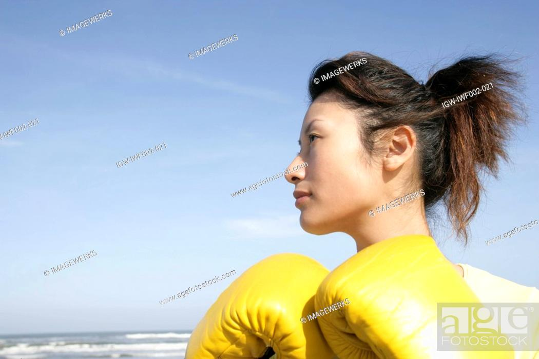 Stock Photo: A side view of a woman wearing boxing gloves seen near the sea.