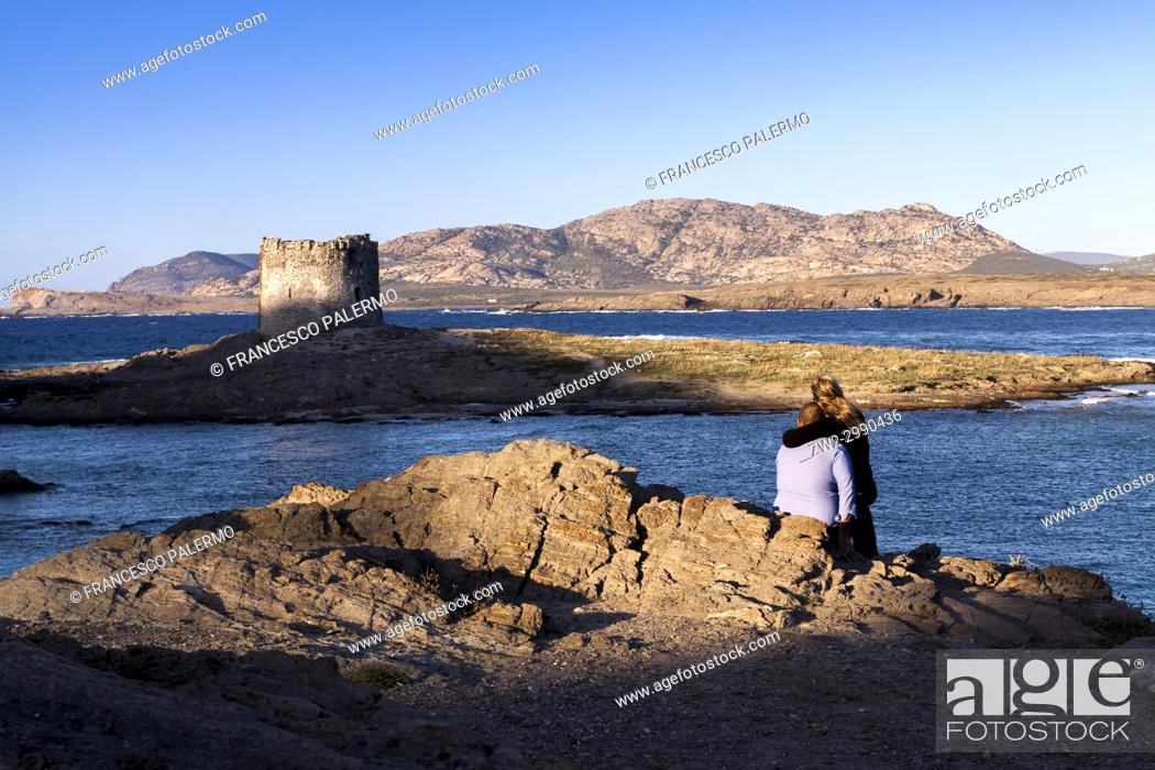 Imagen: Rear view of a couple on rocks looking across sea at derelict lighthouse at dusk. La Pelosa, Sardinia. Italy.