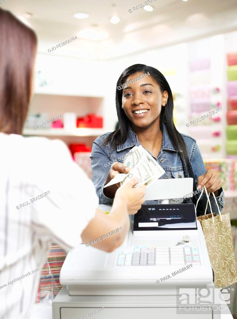 Stock Photo: Woman paying for items at a cashier in store.