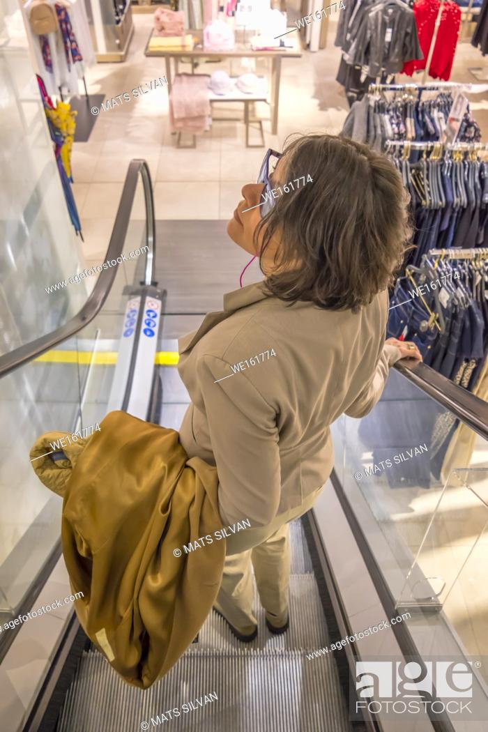 Stock Photo: Woman with her Overcoat Hanging on the Arm in a Escalator.