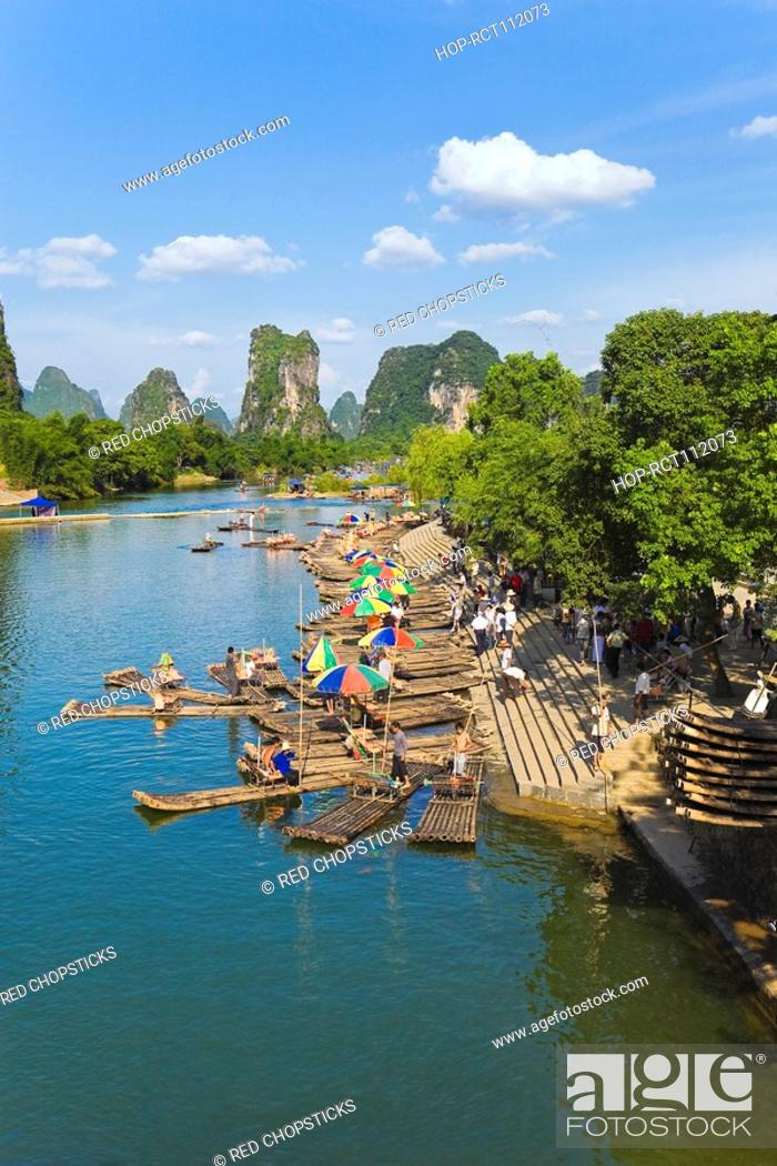 Stock Photo: High angle view of wooden rafts at a riverbank with a hill range in the background, Guilin Hills, XingPing, Yangshuo, Guangxi Province, China.