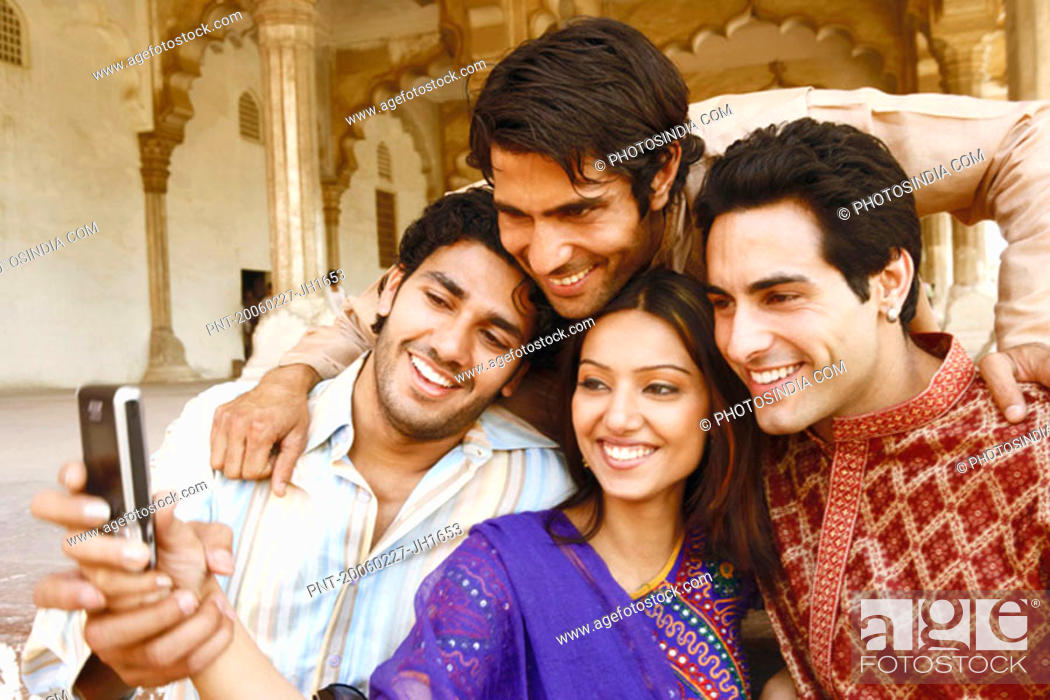 Stock Photo: Close-up of three young men and a young woman looking at a mobile phone, Agra, Uttar Pradesh, India.