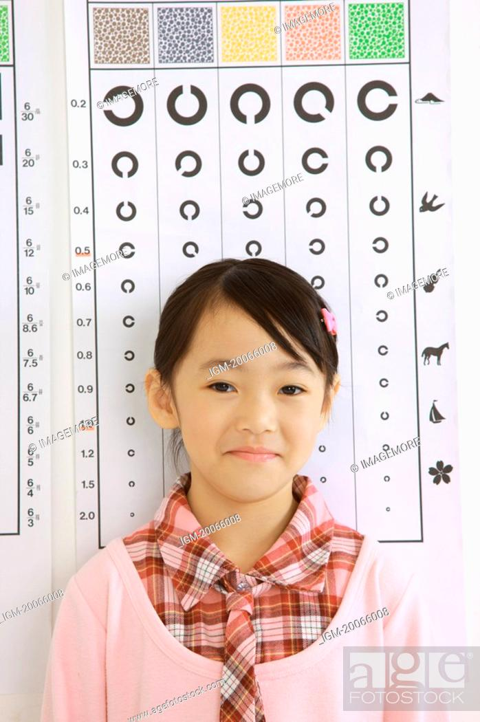 Stock Photo: Little girl standing before eye chart and smiling.