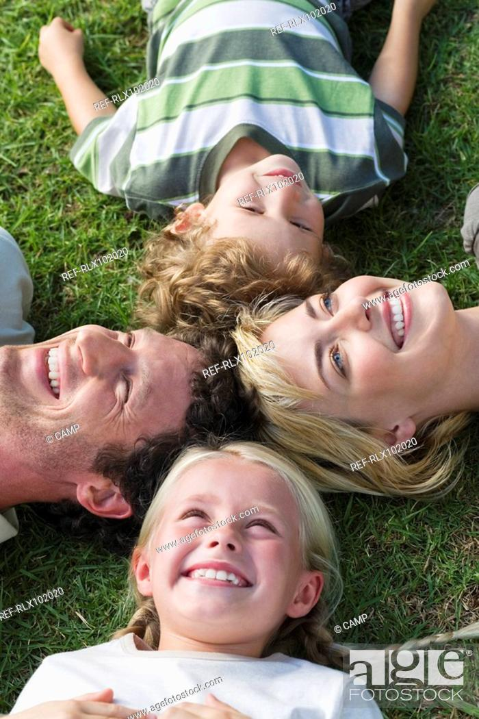 Stock Photo: Family with two children lying on grass, looking up, overhead view.