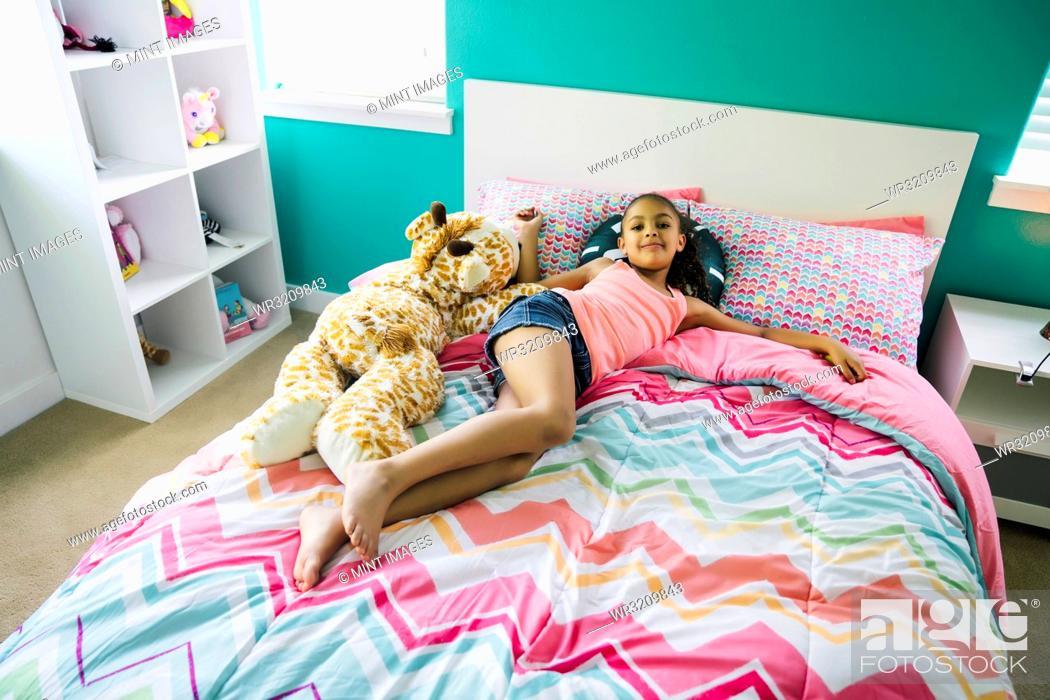 Stock Photo: Tween girl relaxing on her bed in her bedroom.