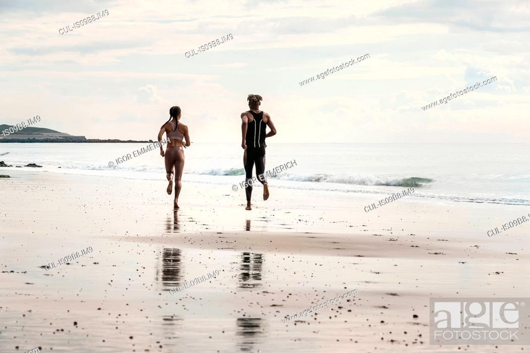 Stock Photo: Rear view of young male and female runners running barefoot along beach.