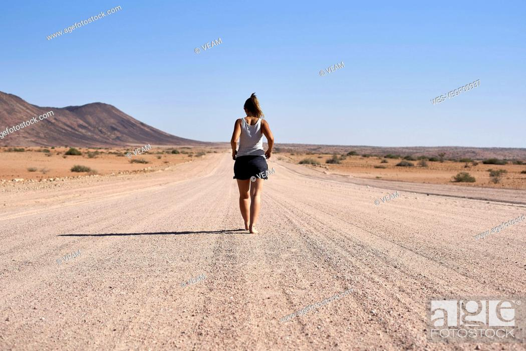 Stock Photo: Woman walking in the middle of a dirt road, Damaraland, Namibia.