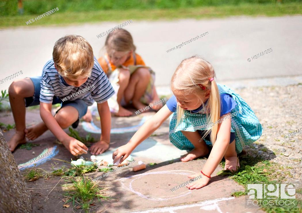Stock Photo: Germany, Bavaria, Group of children drawing on walkway with chalk.