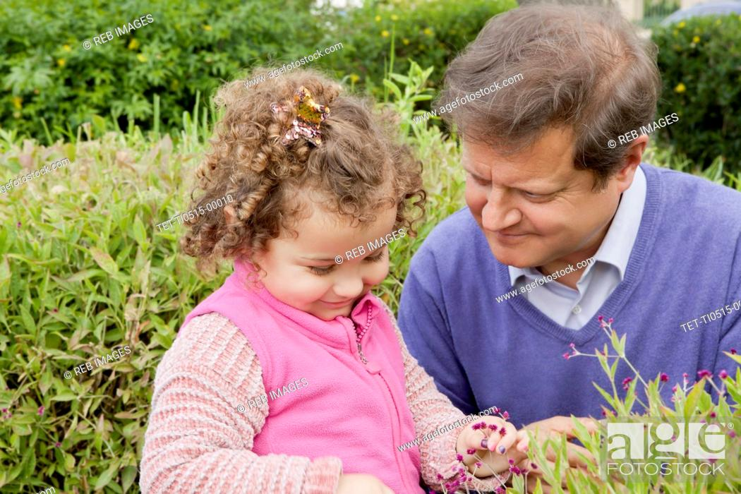 Stock Photo: Girl in garden with her father.