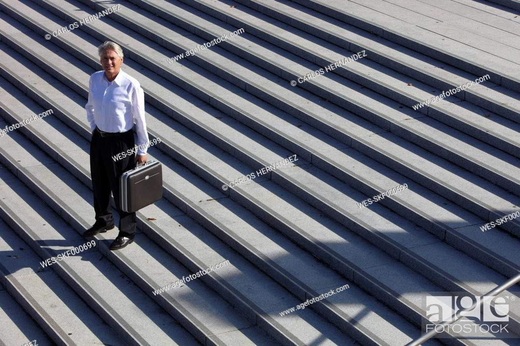 Stock Photo: Germany, Bavaria, Munich, Businessman standing on stairs with briefcase, portrait.