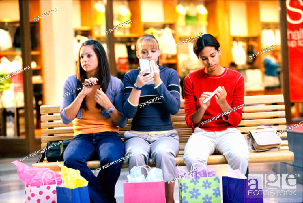 Stock Photo: Three teenage girls sitting on a bench in a shopping mall applying make-up.