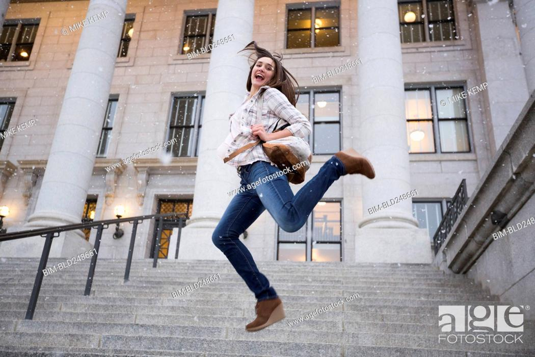 Stock Photo: Caucasian woman carrying backpack jumping in snow on staircase.