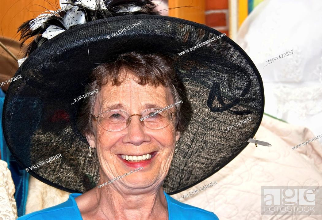 Stock Photo: This happy and active elderly woman in her seventies is smiling while trying on a big black vintage hat while shopping.