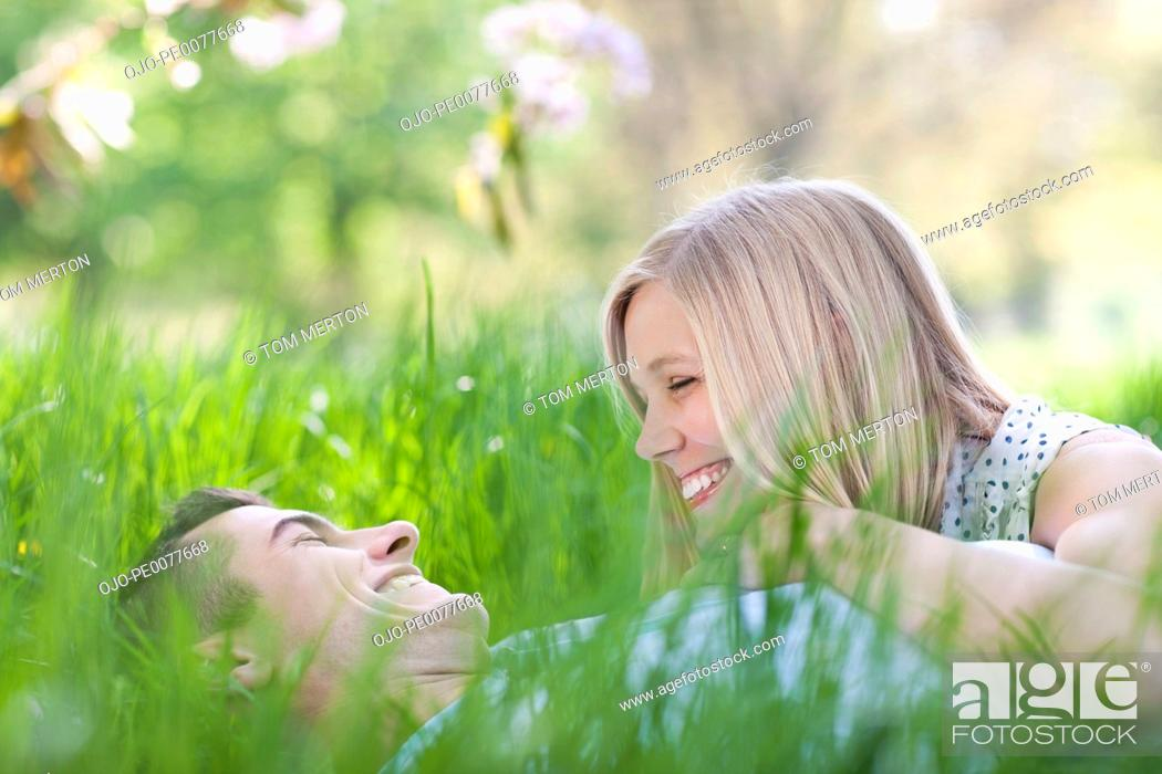 Stock Photo: Smiling couple laying in grass.