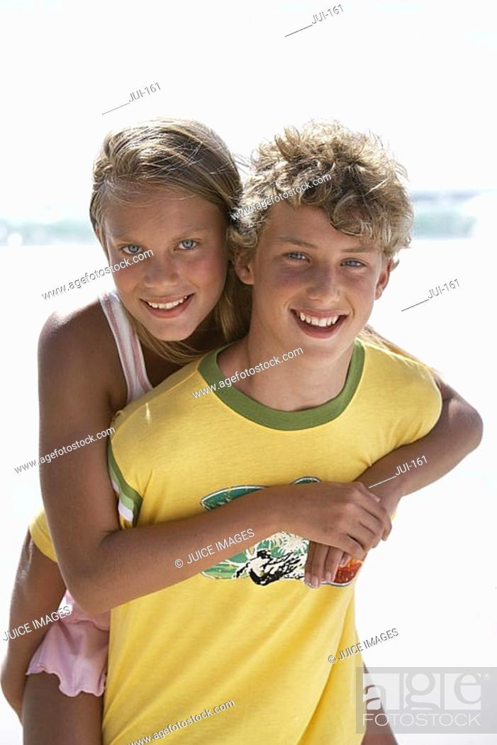 Stock Photo: Boy 12-14 carrying girl 12-14 by piggyback on sandy beach, smiling, portrait.