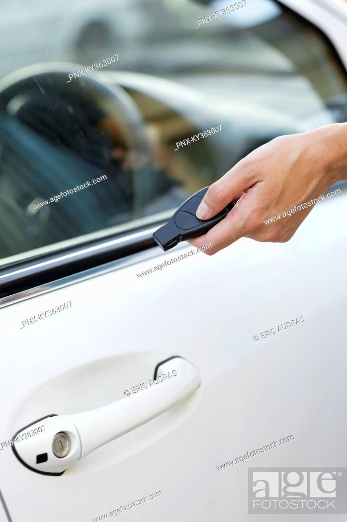 Stock Photo: Person's hand unlocking the car with remote control.