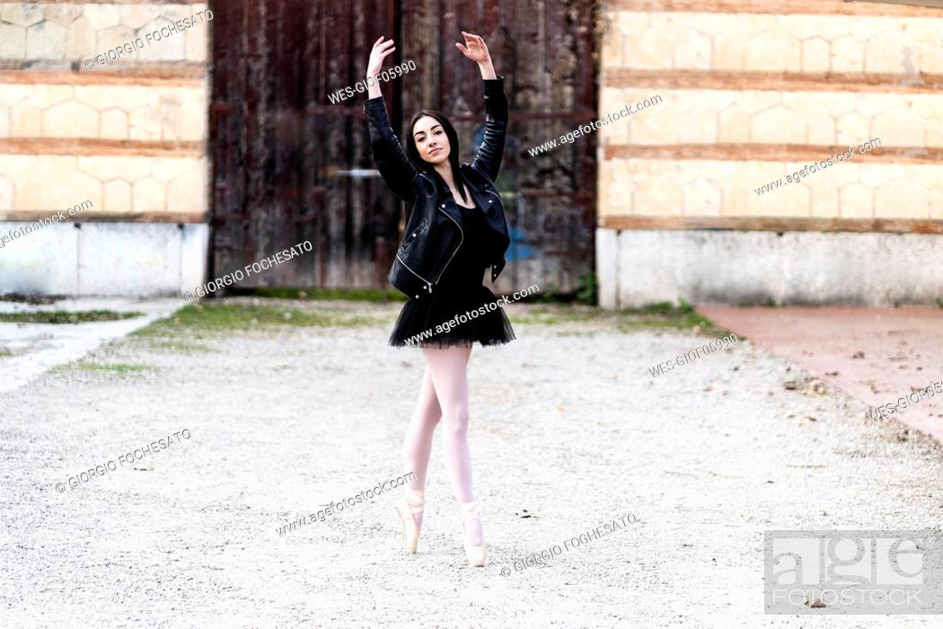 Stock Photo: Italy, Verona, portrait of Ballerina dancing in the city wearing leather jacket and tutu.
